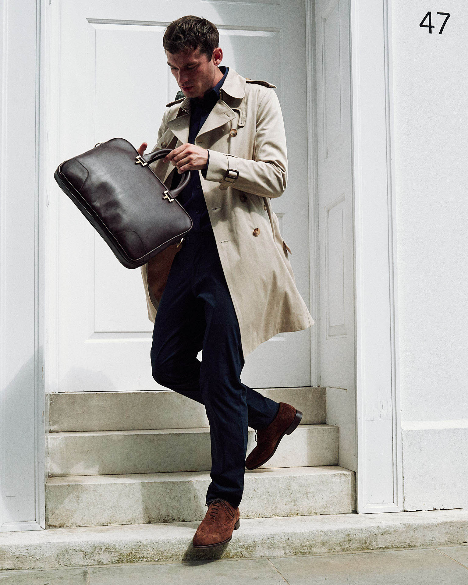 Man in raincoat and holdall  by fashion photographer Tim Cole