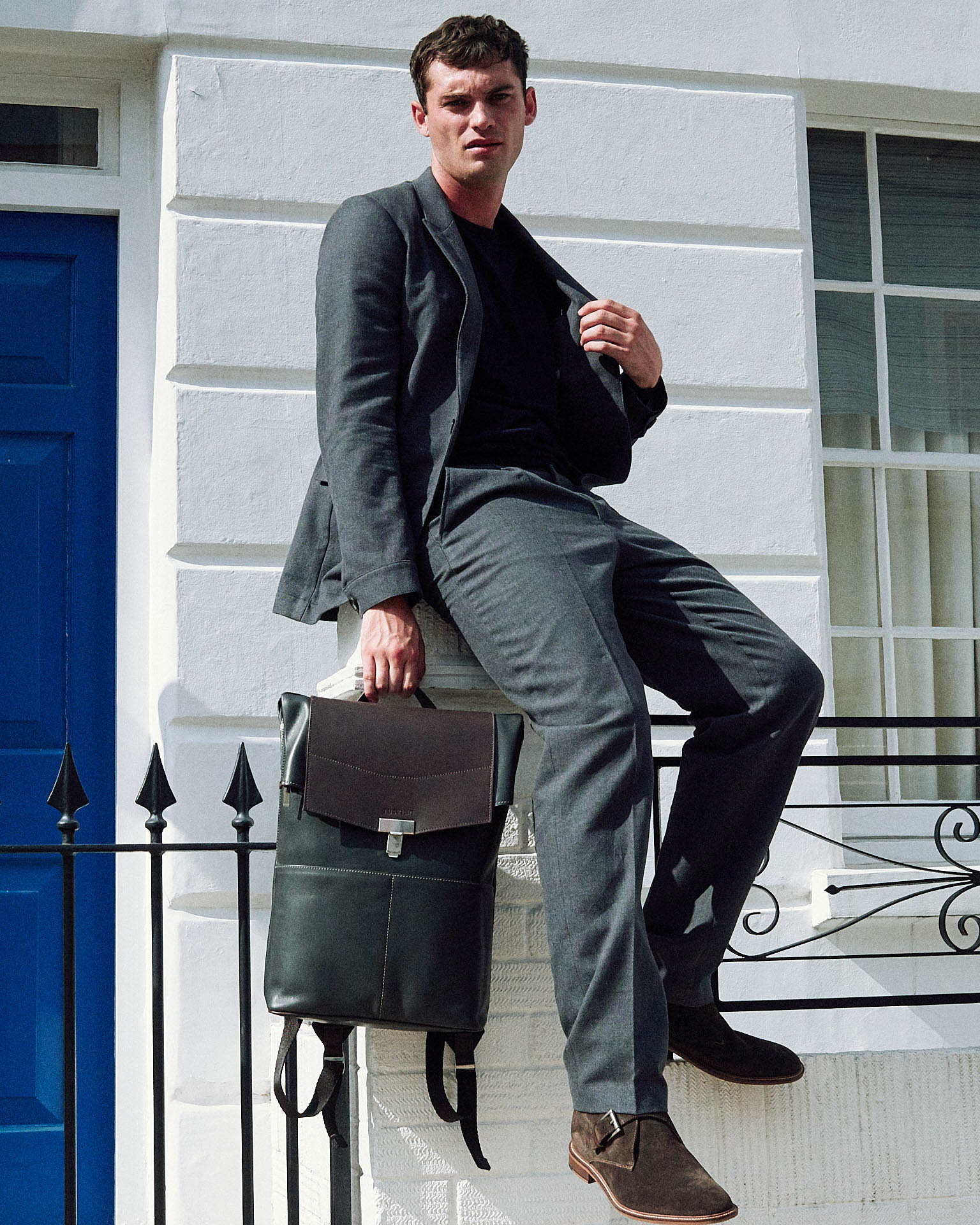 Man in grey suit, sits on white wall holding leather bag by lifestyle photographer Tim Cole
