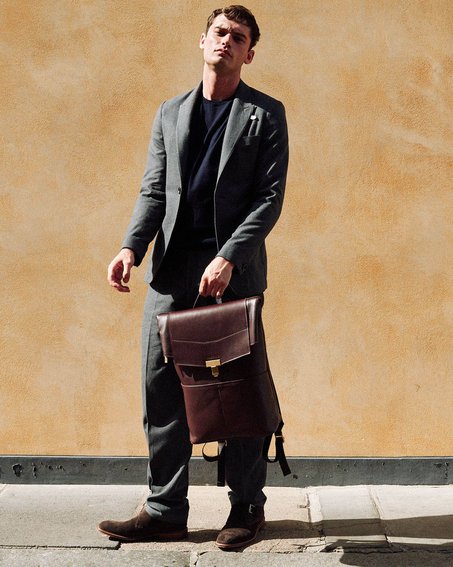 man, bag, orange wall by lifestyle photographer Tim Cole