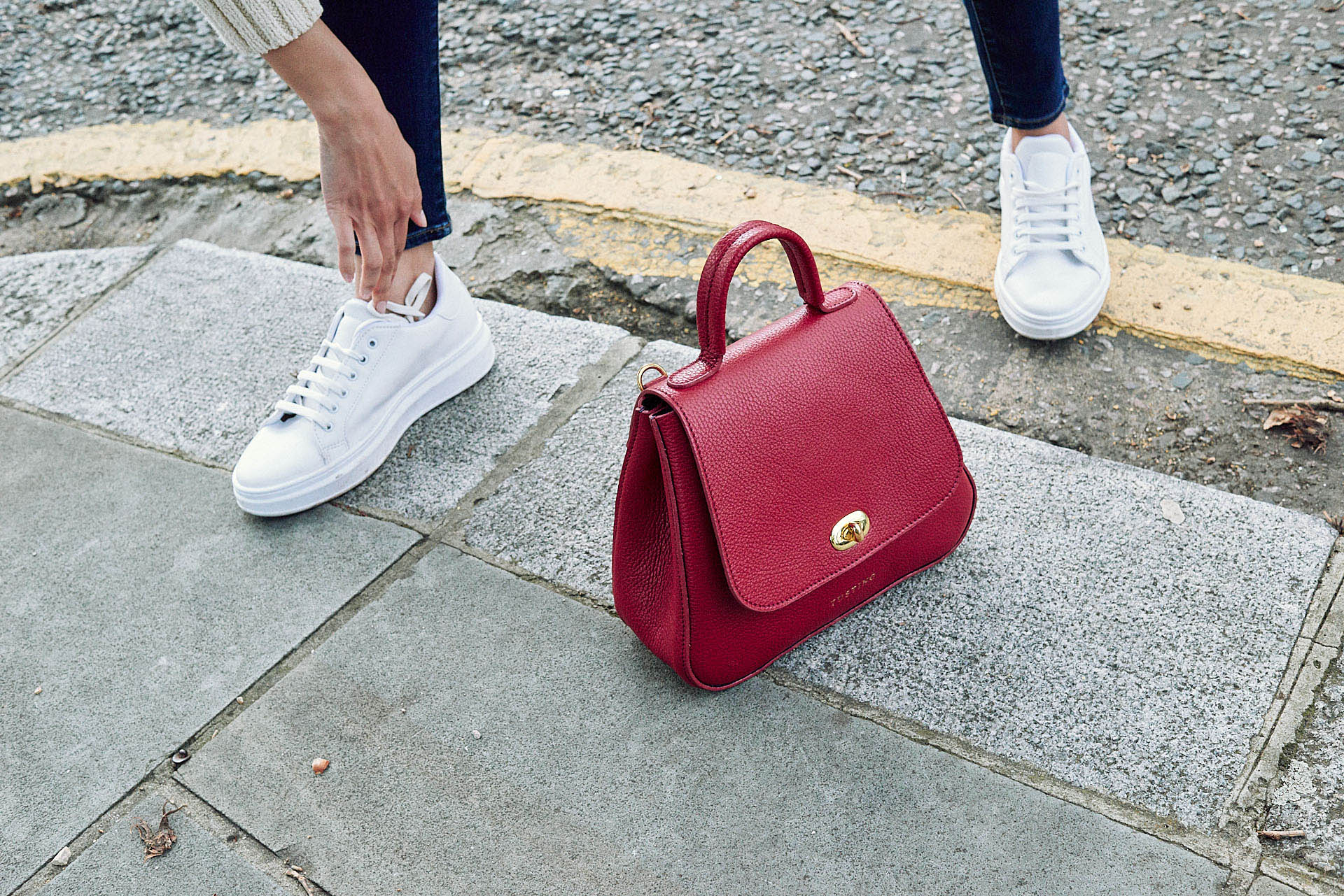 Tusting  red  handbag on pavement, by photographer Tim Cole