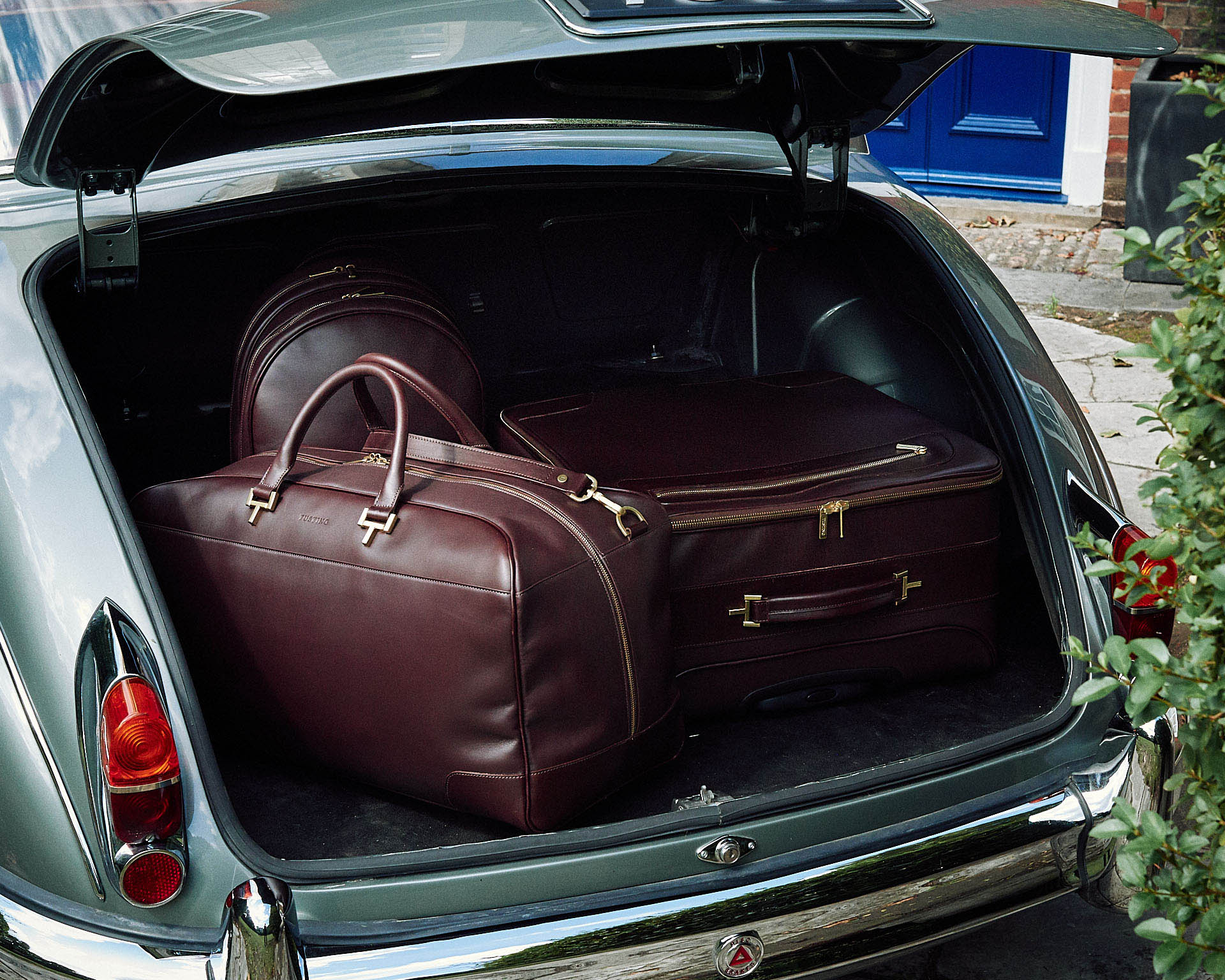 Leather bags in boot of classic jaguar by lifestyle photographer