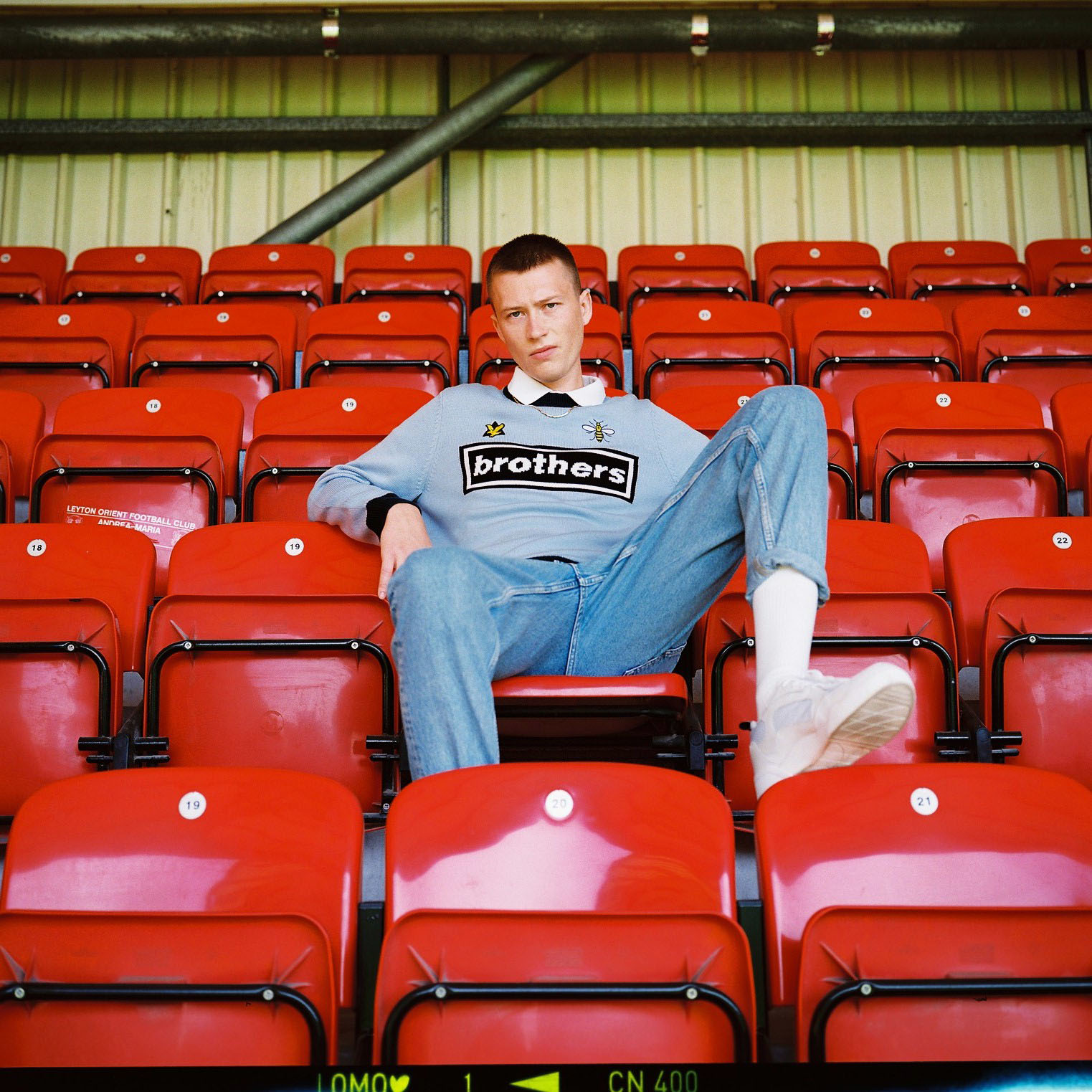 Lad  on red stadium chair by lifestyle photographer Tim Cole