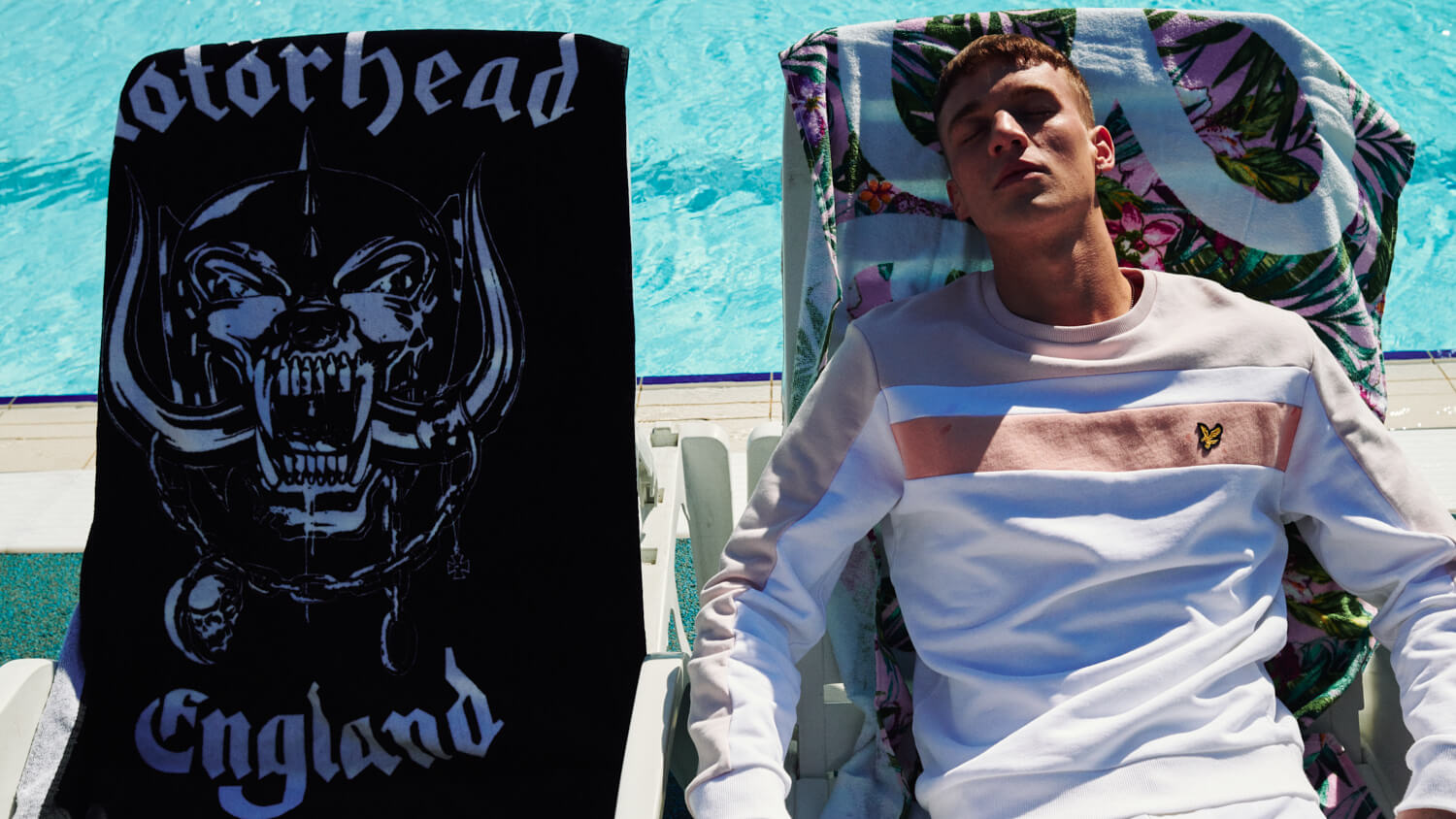 Lad  sits on sunlounger next to motorhead towel