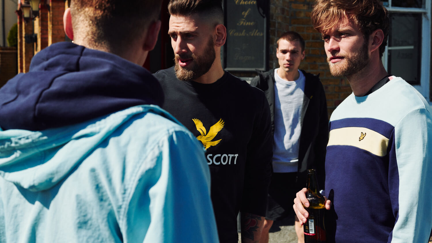 Group of lads stand outside pub by lifestyle photographer Tim Cole