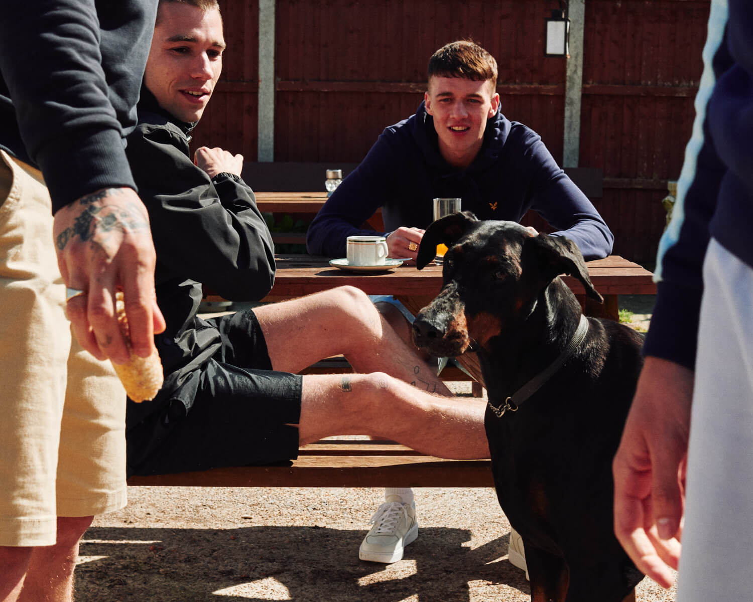 lads in summer sorted  Lyle and Scott feed dog in pub beer garden