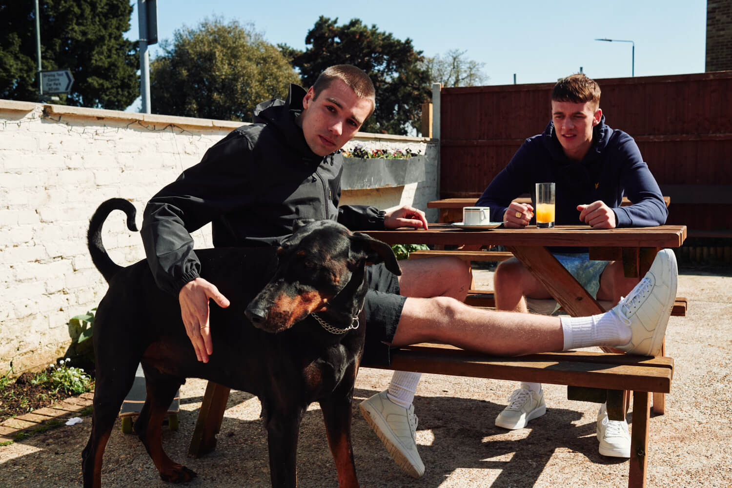 Two lads  in beer garden,  dog by lifestyle photographer Tim Cole