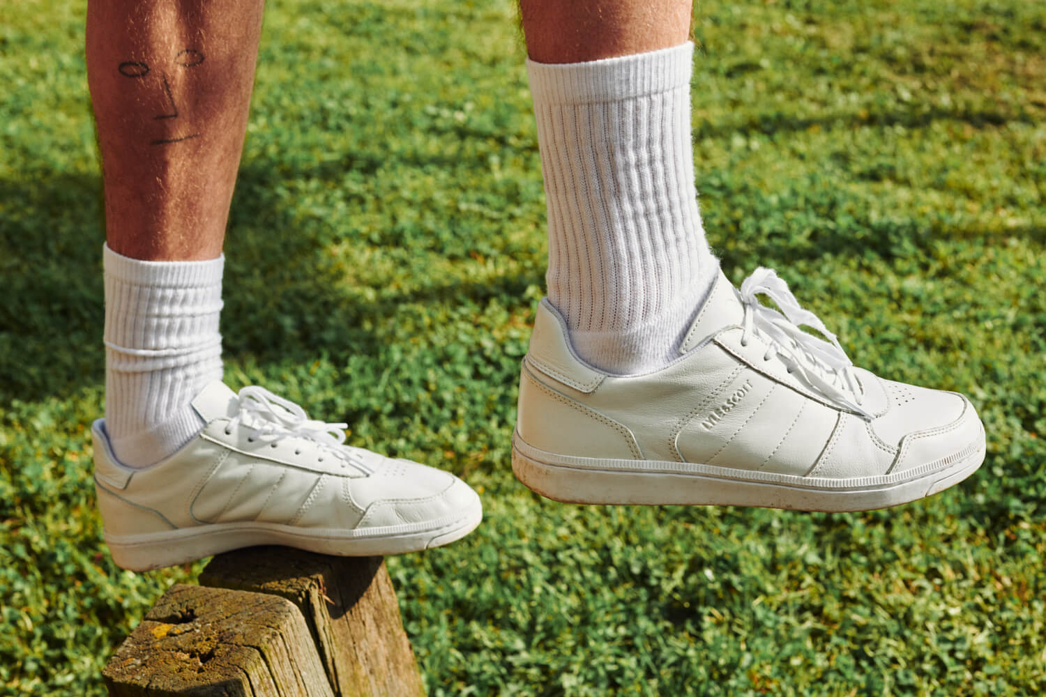 Socks and feet in white Lyle and Scott against grass