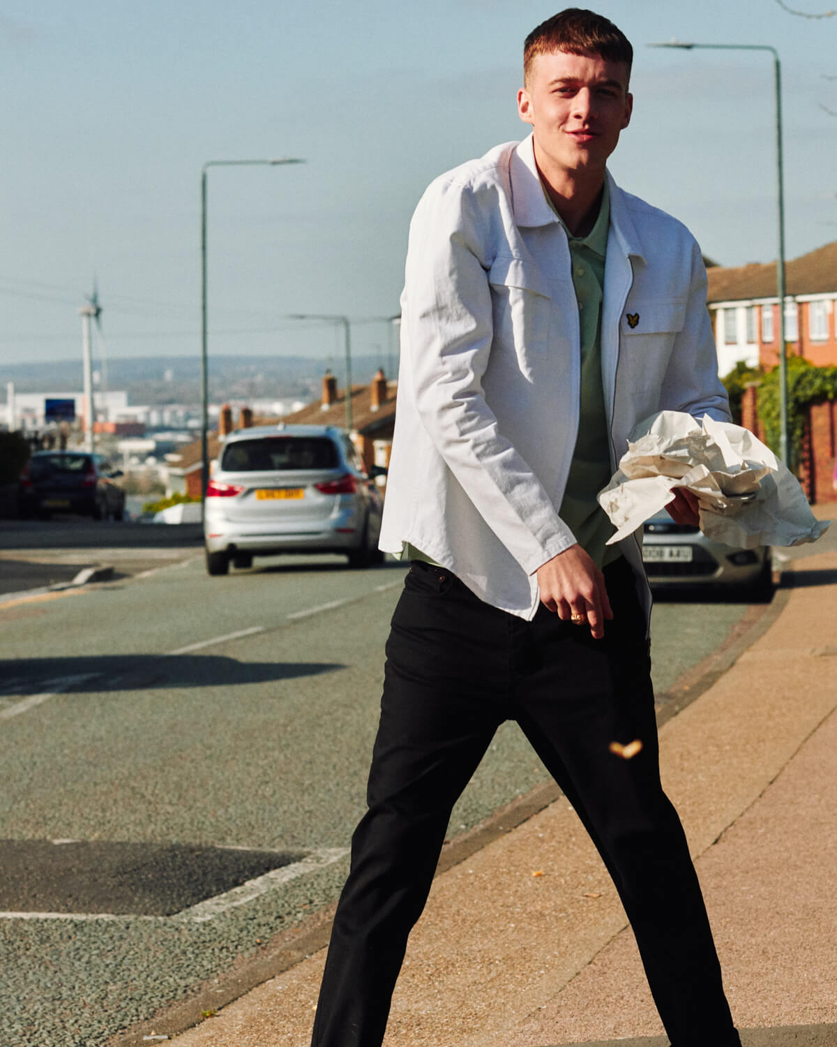 Lad in  eats chips in the street, by lifestyle photographer Tim Cole