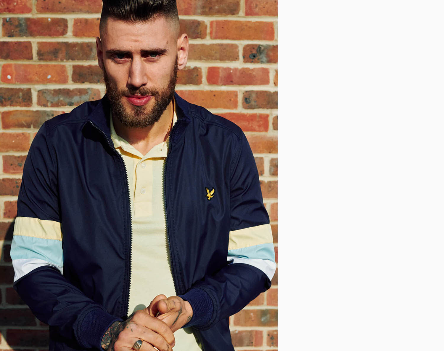 Lyle and Scott lad, brick wall by  lifestyle photographer Tim Cole