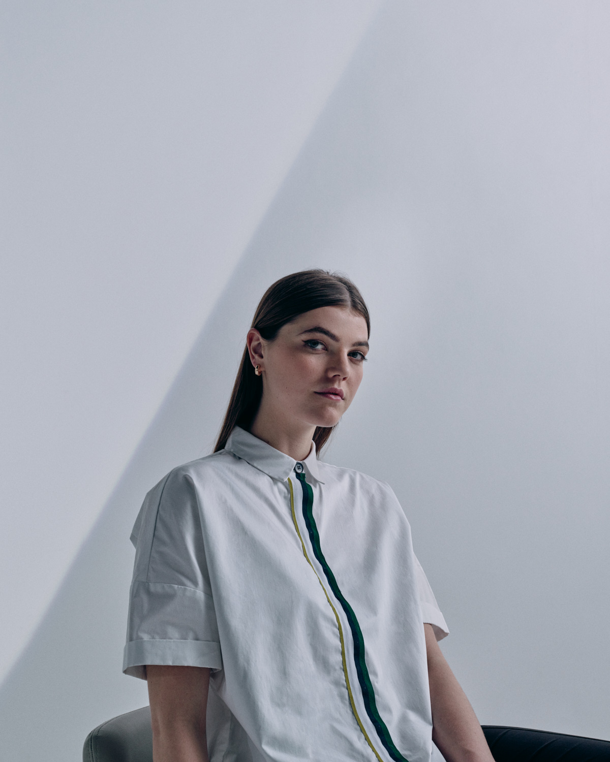 Young woman, white shirt, grey backdrop, diagonal line by London portrait photographer Tim Cole