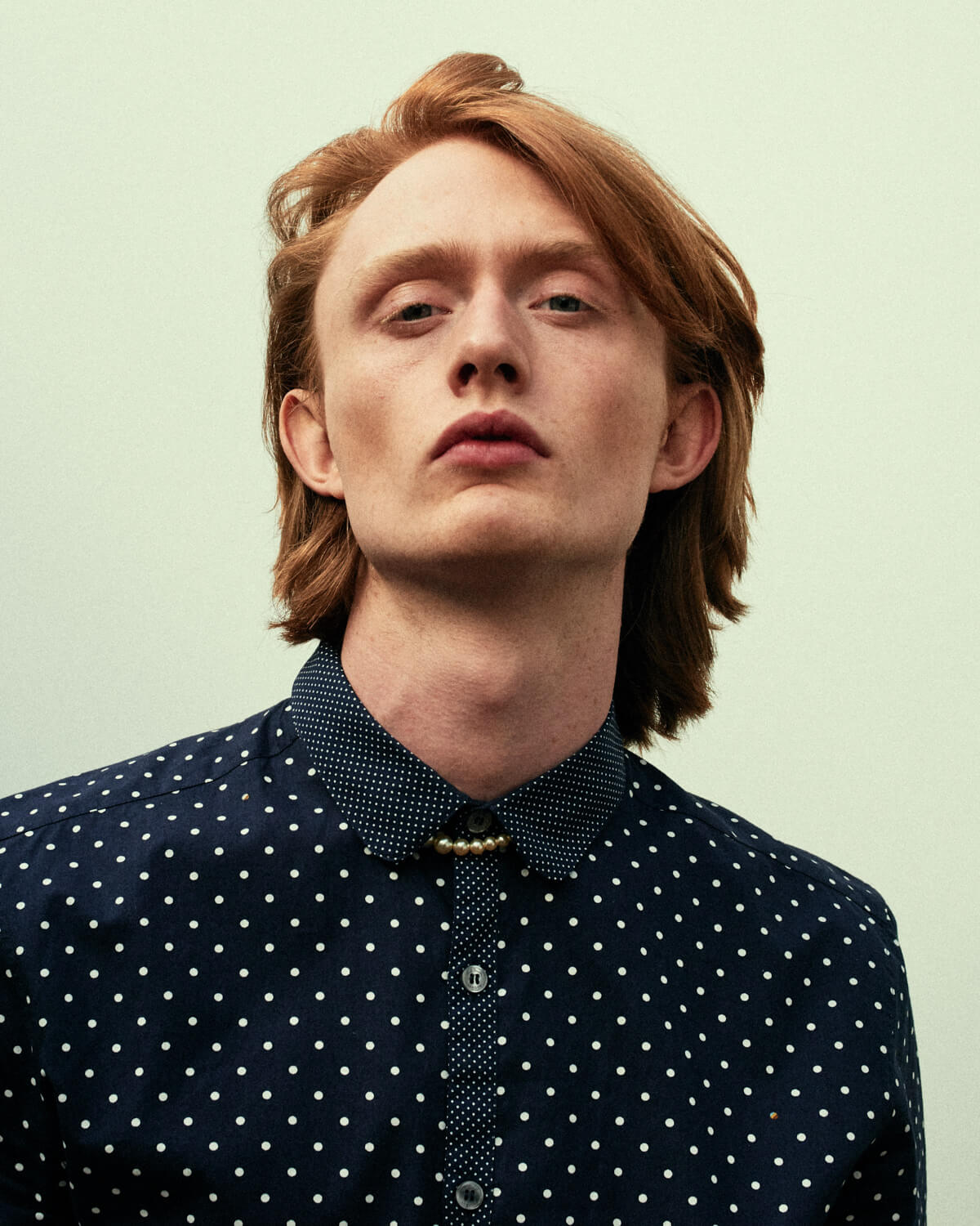 Lad, red hair, spotted shirt, looks to camera in studio by lifestyle photographer Tim Cole