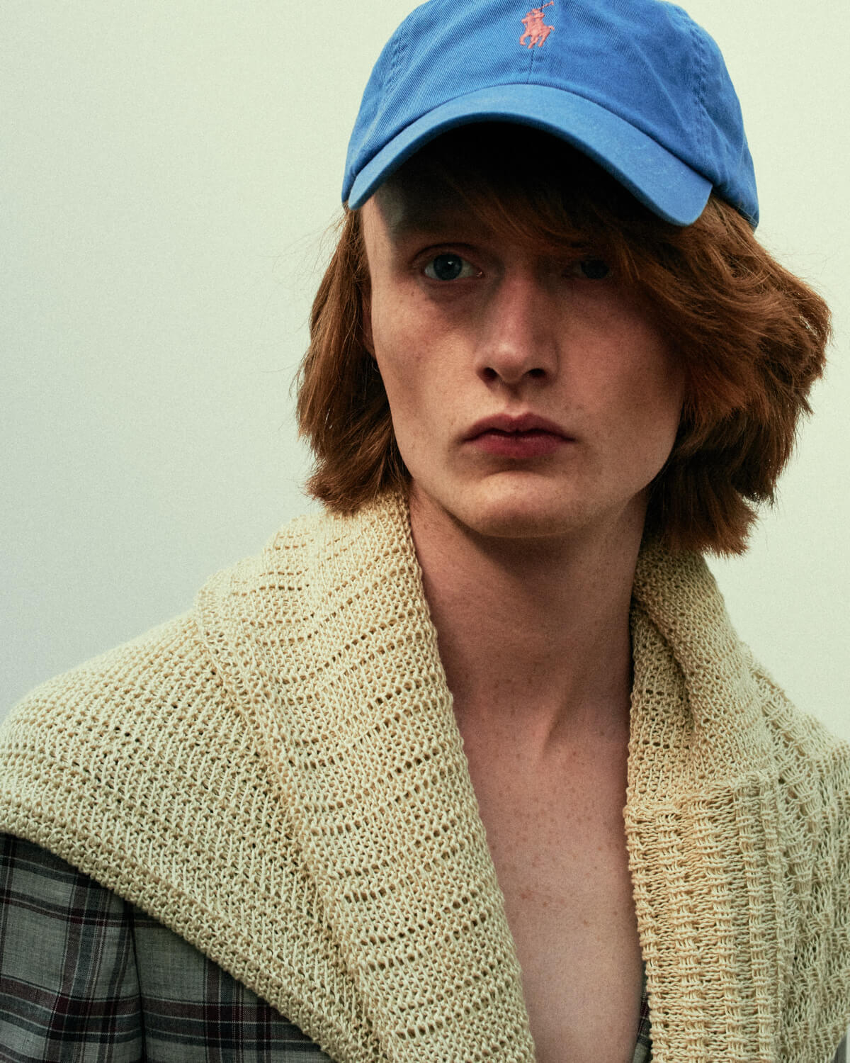 Lad,  beige jumper, blue cap by lifestyle photographer Tim Cole