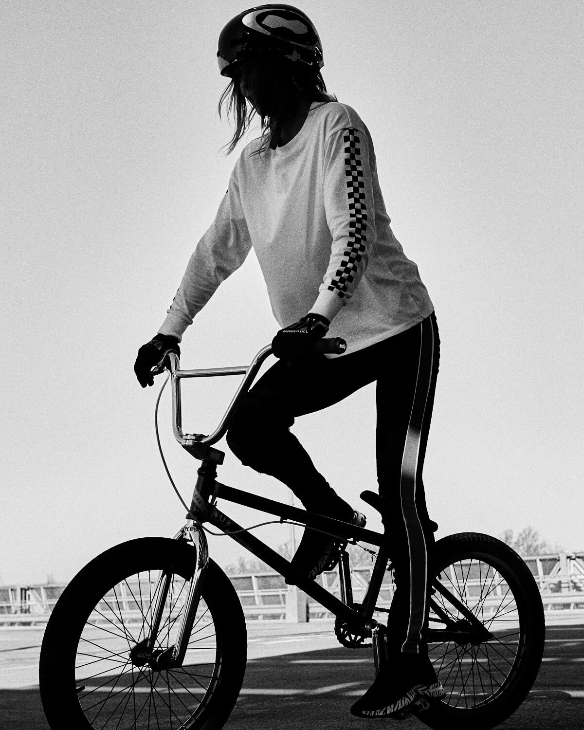B/W, BMX young girl rides bike in car park