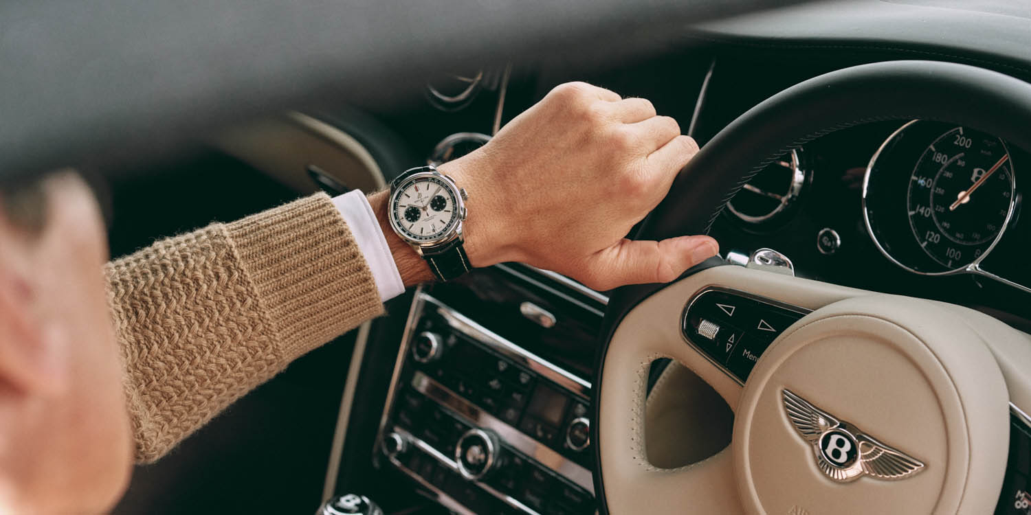 hand holds wheel in Bentley, by lifestyle photographer by Tim Cole