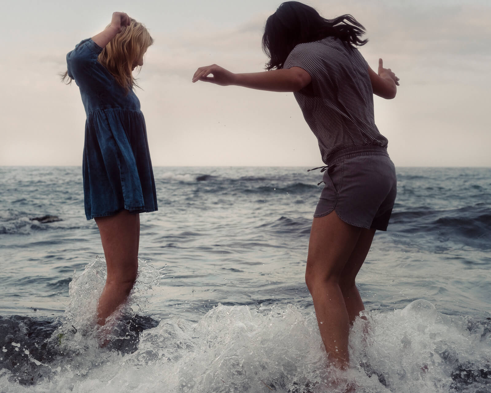 Two millennial girls, summer clothes paddle in Carlyon Bay at dusk lifestyle photographer Tim Cole