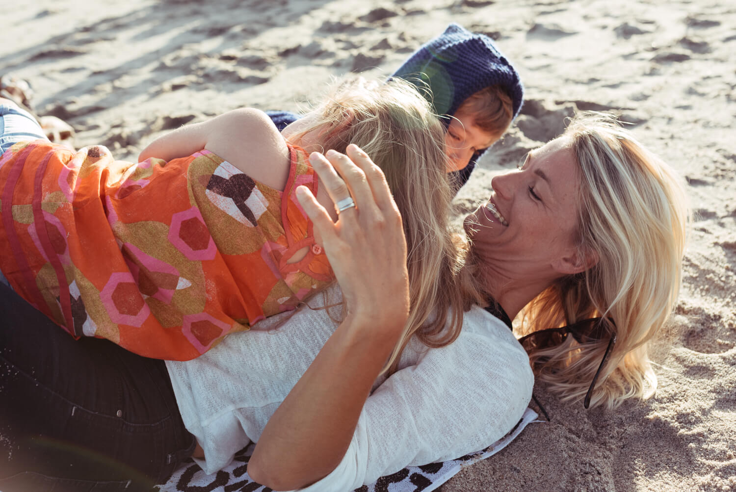 Mother two kid, on sandy beach by lifestyle photographer Tim Cole