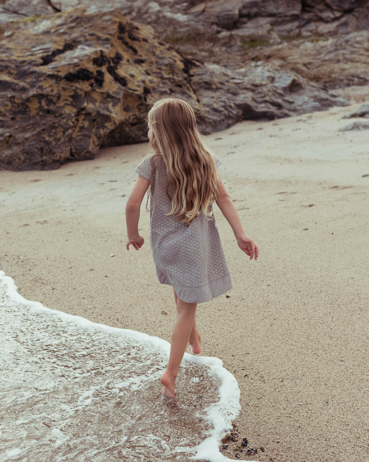 girl, walks away, sandy beach by  lifestyle photographer Tim Cole