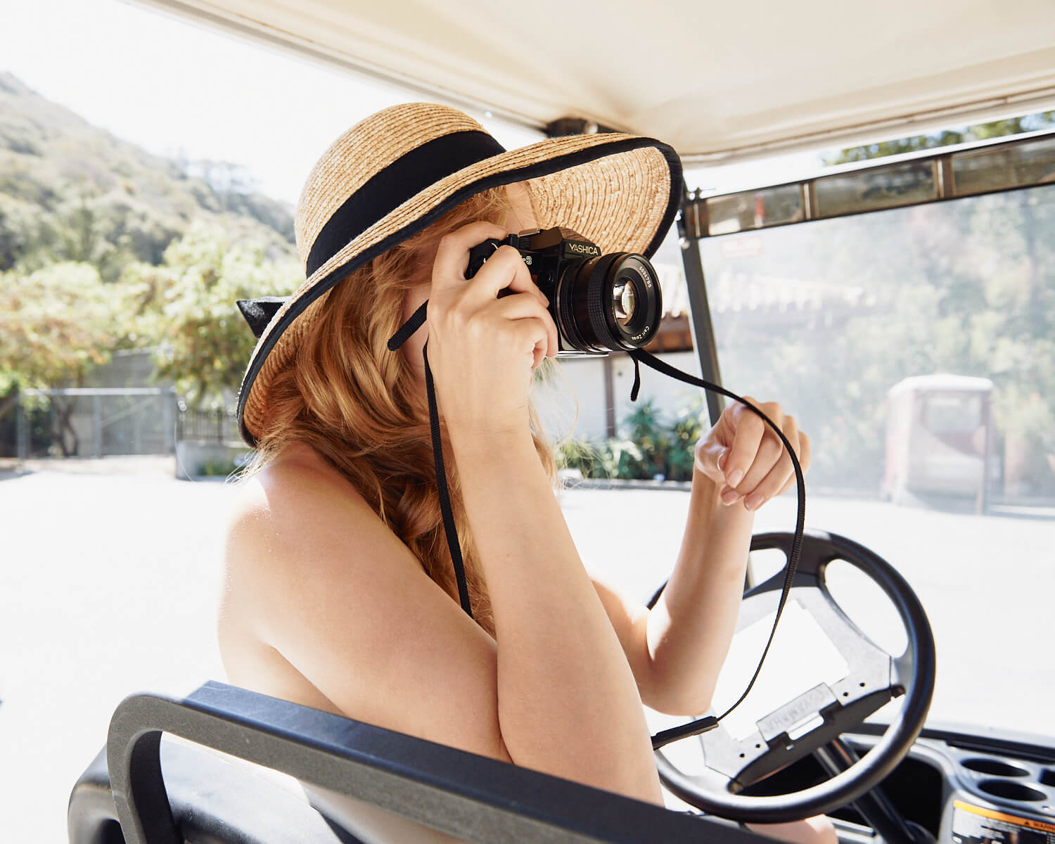 Young woman, in golf cart, by lifestyle photographer Tim Cole