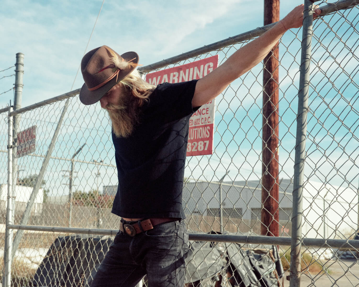 hipster hangs off wired gate by lifestyle photographer Tim Cole
