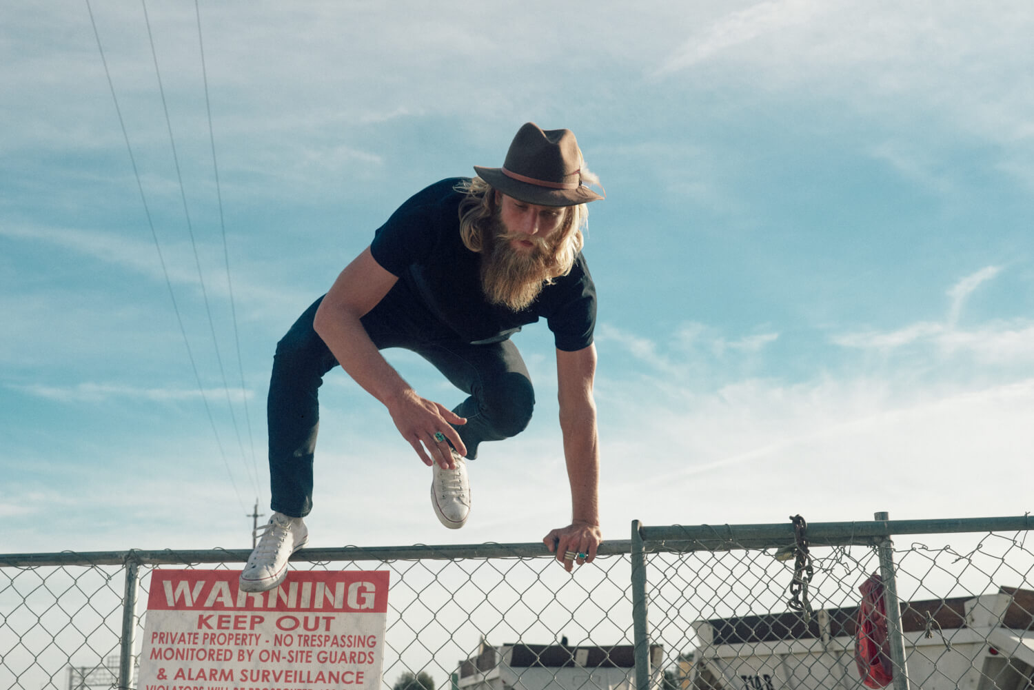 bearded hipster jumps wire by lifestyle photographer Tim Cole