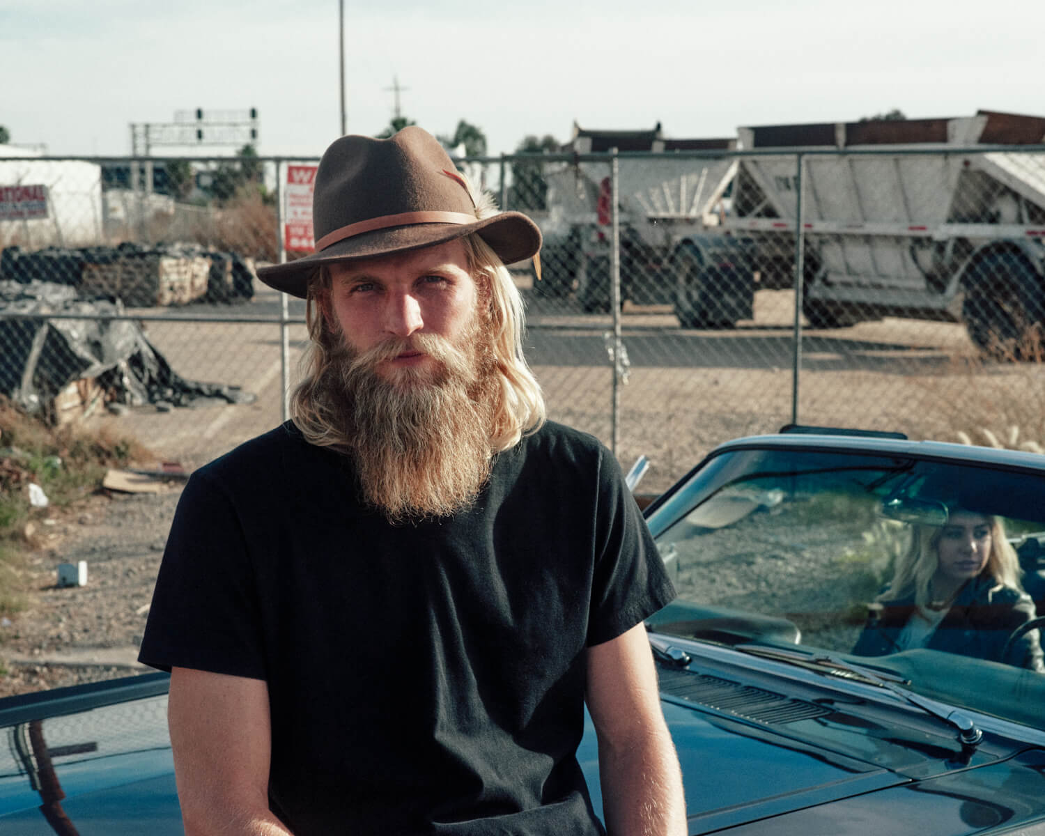 hipster sits on hood by lifestyle photographer Tim Cole
