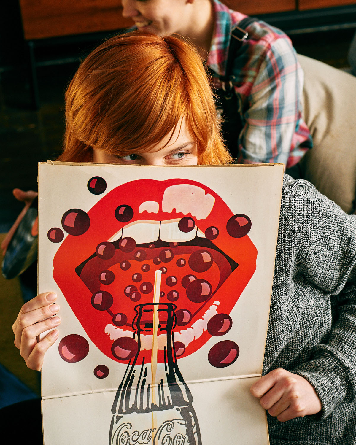 Teenage girl, red hair holds up vinyl album illustrated lips, by lifestyle photographer Tim Cole