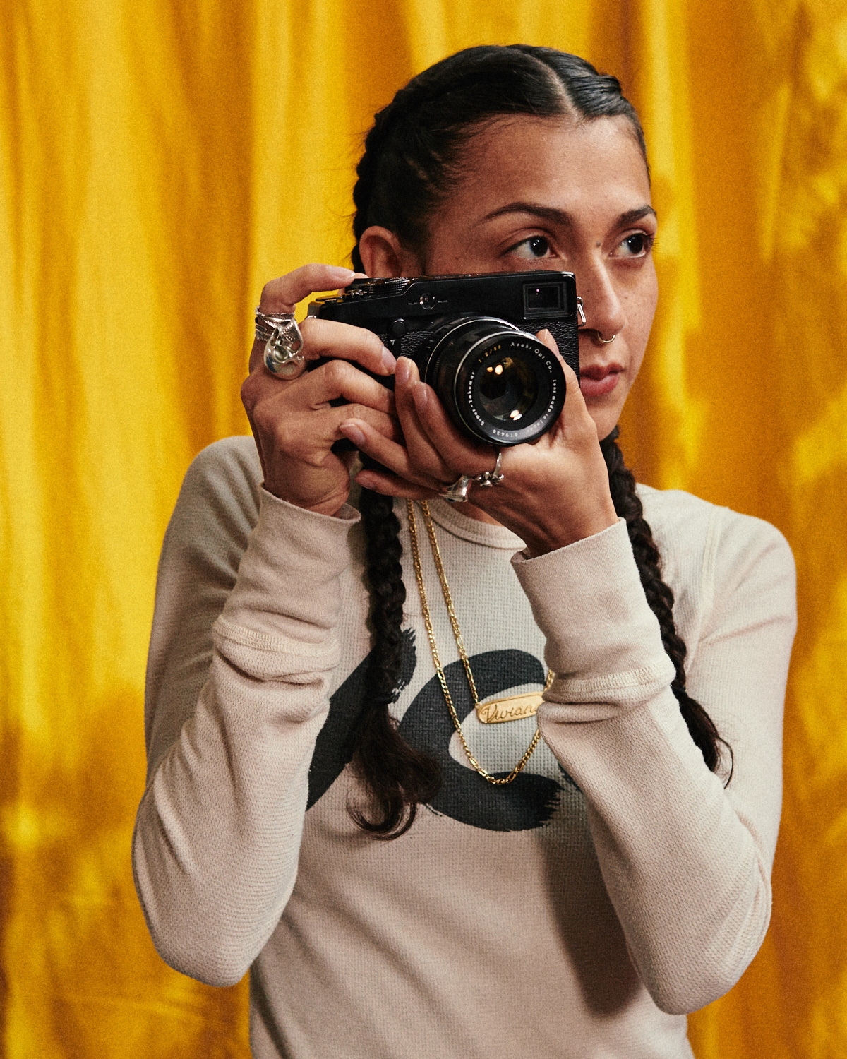 Hipster girl, holds up camera by yellow curtain by lifestyle photographer Tim Cole