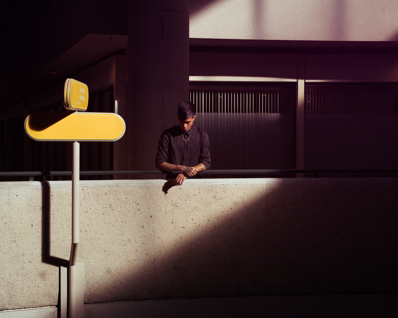 Guy in black,  hotel atrium by lifestyle photographer Tim Cole
