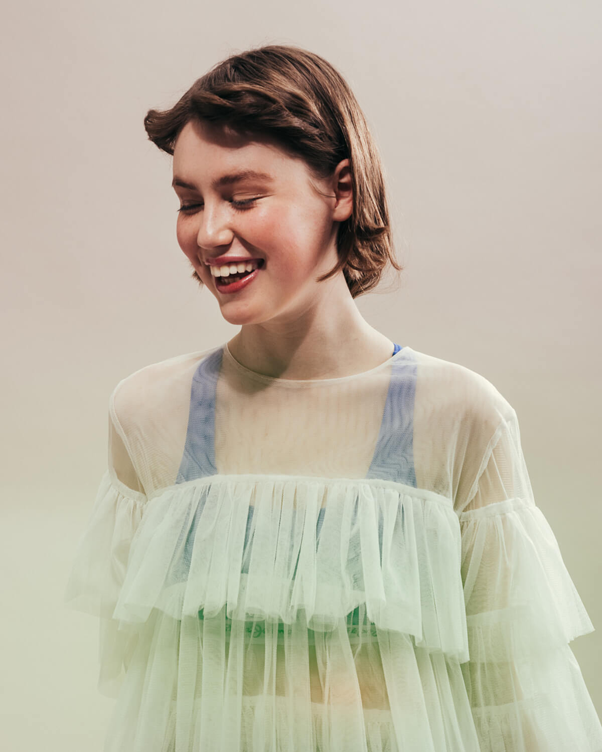 Girl smiley,, frilly sheer top,  by portrait photographer Tim Cole