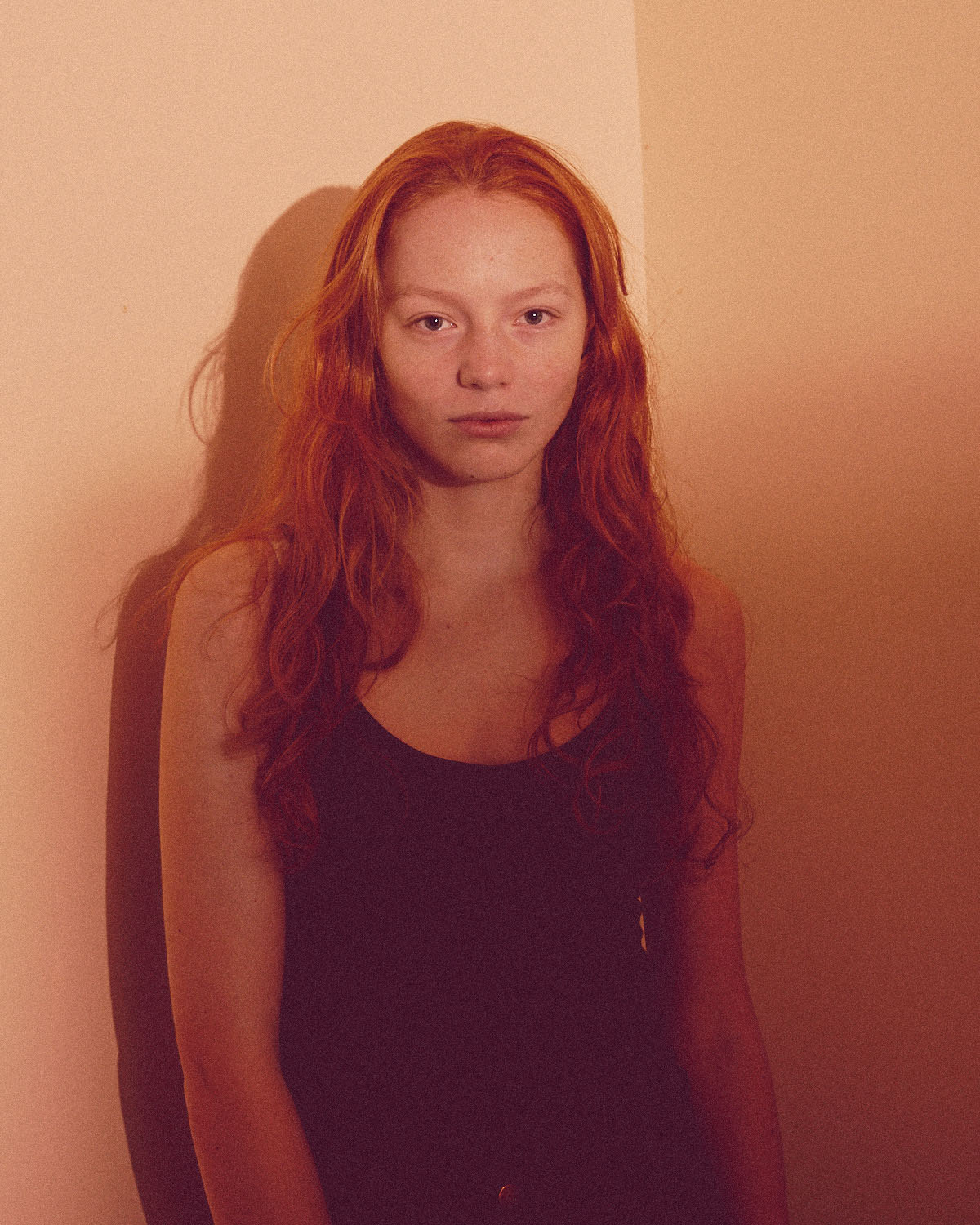 Girl, ginger hair, beige wall by portrait photographer Tim Cole