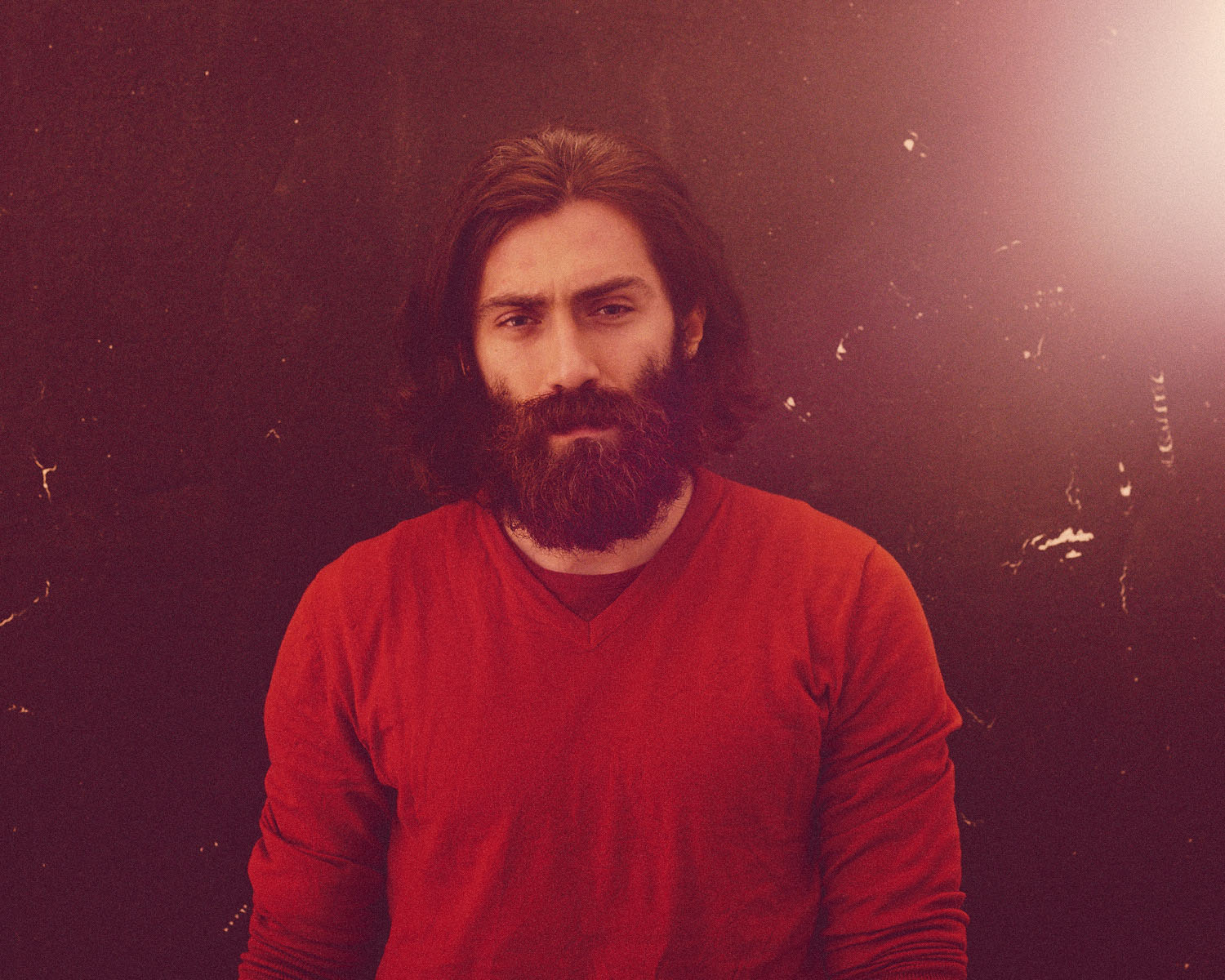 Bearded man, red jumper, by portrait photographer Tim Cole